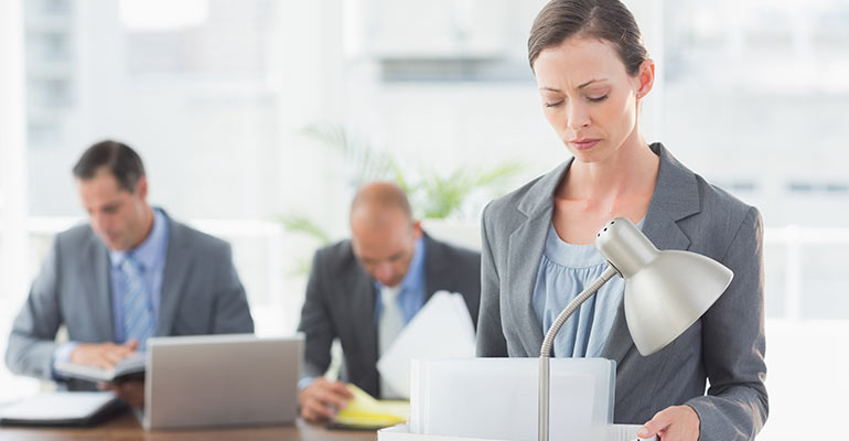 woman carrying box out of office with male employees in background