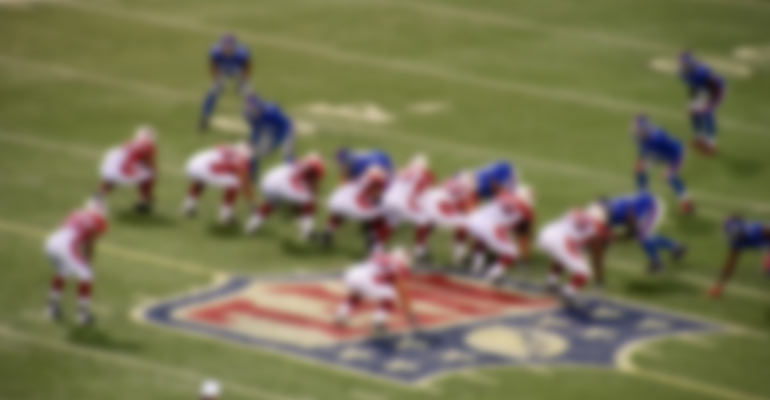 blurred photo of NFL logo and game