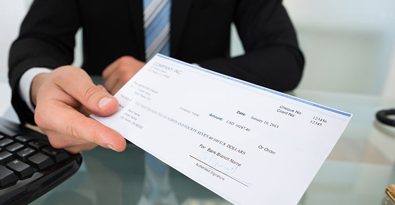 Man sitting at desk holding a check