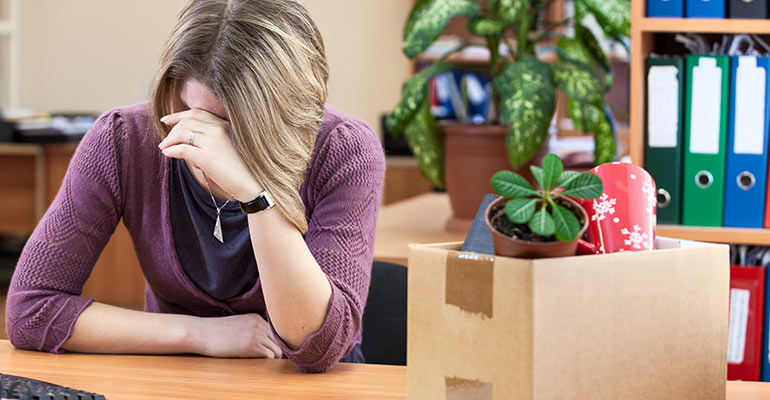 worried woman sitting at desk with box of belongings looking down